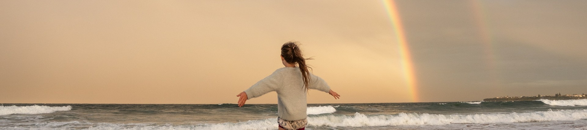 Anonymous woman on beach with rainbow